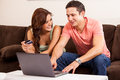 Buying something online cute hispanic couple using a credit card and a laptop computer to buy Royalty Free Stock Photography