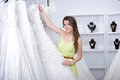 Buying wedding dress smiling pretty bride chooses white gown at shop of fashion Royalty Free Stock Images