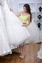 Buying wedding dress smiling pretty bride chooses white gown at shop of fashion Royalty Free Stock Photo