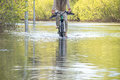 Bycyclist with naked feet try to overcome water during a flood in springtime Royalty Free Stock Photo