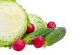 Cabbage cut in half closeup, two cucumbers and red radish Royalty Free Stock Photo