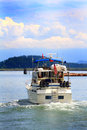 Cabin cruiser cruising a just off shore at hope island state park in puget sound washington Stock Photos