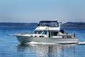 Cabin cruiser a running just off shore at hope island state park in puget sound washington Royalty Free Stock Photo
