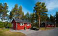 Cabins in swedish camp site wooden rural with old car parked foreground sweden Stock Photo