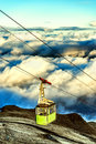 Cable car going up to the top of the mountain over the clouds green Royalty Free Stock Images