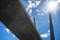 Cable stayed bridge from below against a blue sky with clouds and sun flare in the frame Royalty Free Stock Image