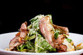 Caesar salad with bacon a white dish and juicy on dark background Royalty Free Stock Images