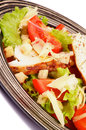 Caesar salad with grilled chicken breast garlic crouton lettuce tomatoes and grated parmesan cheese closeup on striped plate Stock Images