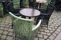 Cafe circle tables and wicker chairs on street pavement. Royalty Free Stock Photo