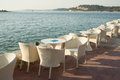 Cafe garden seats empty tables by the sea Royalty Free Stock Photo