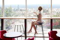 Cafe girl in barcelona young slim beautiful sits on a high bar stool a with stunning panoramic views of siesta break with a cup of Stock Image