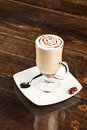 Cafe latte beautifuly decorated cup of and chocolate heart against polished table top Royalty Free Stock Photos