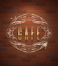 Cafe ornate golden sign on vintage brick wall Stock Photo