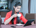Cafe young indian businesswoman on a coffee break using tablet computer Stock Photos