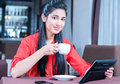 Cafe young indian businesswoman on a coffee break using tablet computer Royalty Free Stock Photo