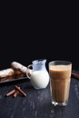 Caffe latte on dark background culinary coffee drinking a tall glass with milk eclair and chocolate sticks a wooden Royalty Free Stock Image