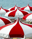 Cagnes sur mer cote d azur alpes maritimes provence alpes france red and white umbrellas on the beach Royalty Free Stock Image
