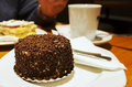 Cake with chocolate sprinkles on a table in cafe Royalty Free Stock Photos
