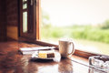 Cake and cup of coffee on wooden table near window sill time with snacks concept a blurred nature background shallow depth Stock Images
