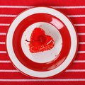 Cake form red heart cherry striped tablecloth top view Royalty Free Stock Photo