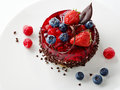 Cake with fresh berries and chocolate on white plate Stock Photos