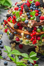 Cake made of wild fresh berry fruits on old wooden table Stock Photo