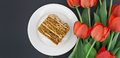 Cake slice with nut on plate. Bouquet of tulips. Top view Royalty Free Stock Photo
