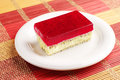 Cake with strawberry jelly and poppy in a plate on colorful bamboo napkin Royalty Free Stock Images