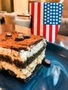Cup of coffee with USA flag print and tasty cream cake Tiramisu