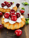 Cakes coconut with whipped cream and sweet cherry shallow dof Stock Images