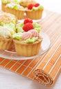 Cakes decorated with raspberries on orange bamboo napkin Royalty Free Stock Image