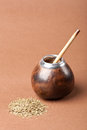 Calabash and bombilla with yerba mate on brown background Stock Photo