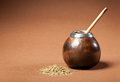 Calabash and bombilla with yerba mate isolated on brown background Royalty Free Stock Photo