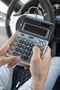 Calculating the car insurance dealer on calculator for a new expensive Stock Photography