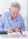 Calculating home budget old man with reading glasses on table Royalty Free Stock Images