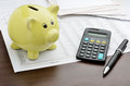 Calculating savings piggy bank with calculator and business reports Royalty Free Stock Image