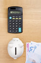 Calculating savings piggy bank euro bills and calculator on a table top view Royalty Free Stock Photography