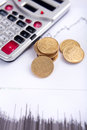 Calculator and coins on chart Royalty Free Stock Photo