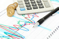 Calculator, coins and pen laying on chart. Stock Photography