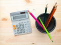 Calculator and desk organizer filled with colored pencils on a wooden background Royalty Free Stock Photography