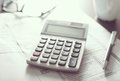 Calculator device on papers with eyeglasses and pen Royalty Free Stock Image
