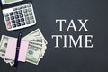 Calculator and Dollars with message TAX TIME Royalty Free Stock Photo