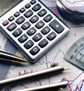 Calculator pen on stock charts and graphs Royalty Free Stock Image