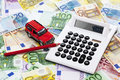 Calculator with pen and toy car on heap of euro notes Royalty Free Stock Photo