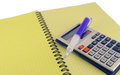 Calculator and pen on the writing book yellow Royalty Free Stock Photo