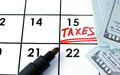 Calendar with word taxes and dollars notes Royalty Free Stock Image