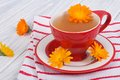Calendula flower tea on striped tablecloth the table Royalty Free Stock Image