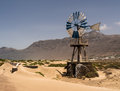 Caleta de farmara lanzarote canary islands windmill and mountain backdrop at beach Stock Photos