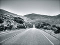Californian road a deserted leading the traveler along the arid mountains in black and white Stock Photos