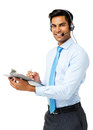 Call center representative writing on clipboard portrait of happy male and wearing headset against white background vertical shot Stock Photo